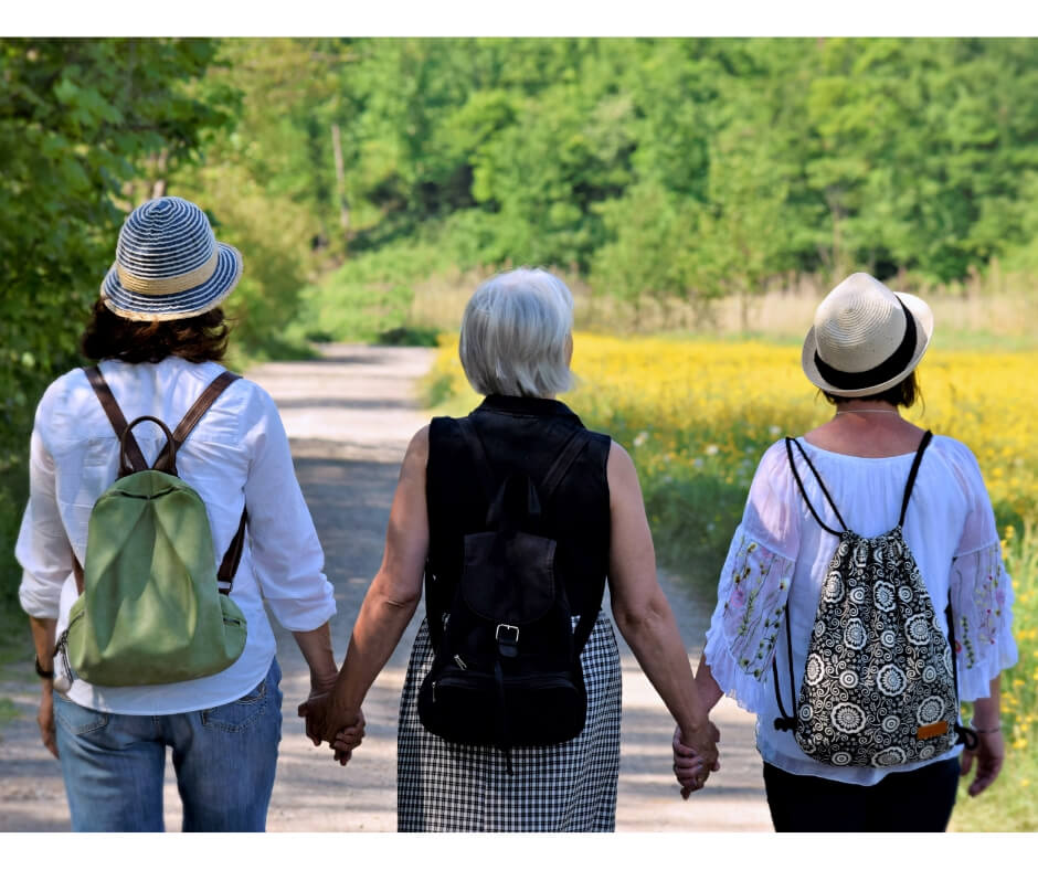 3 middle aged women holding hands