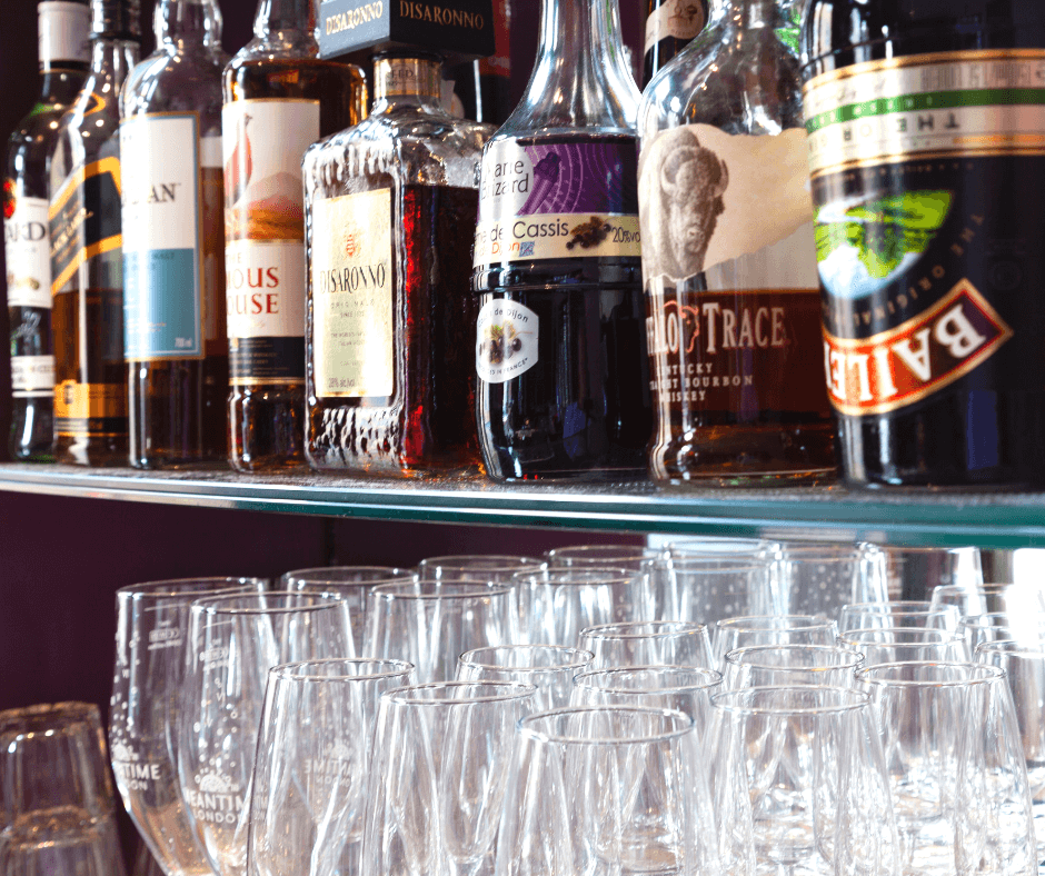 bottles of alcohol and glasses behind bar. all alcohol causes cancer