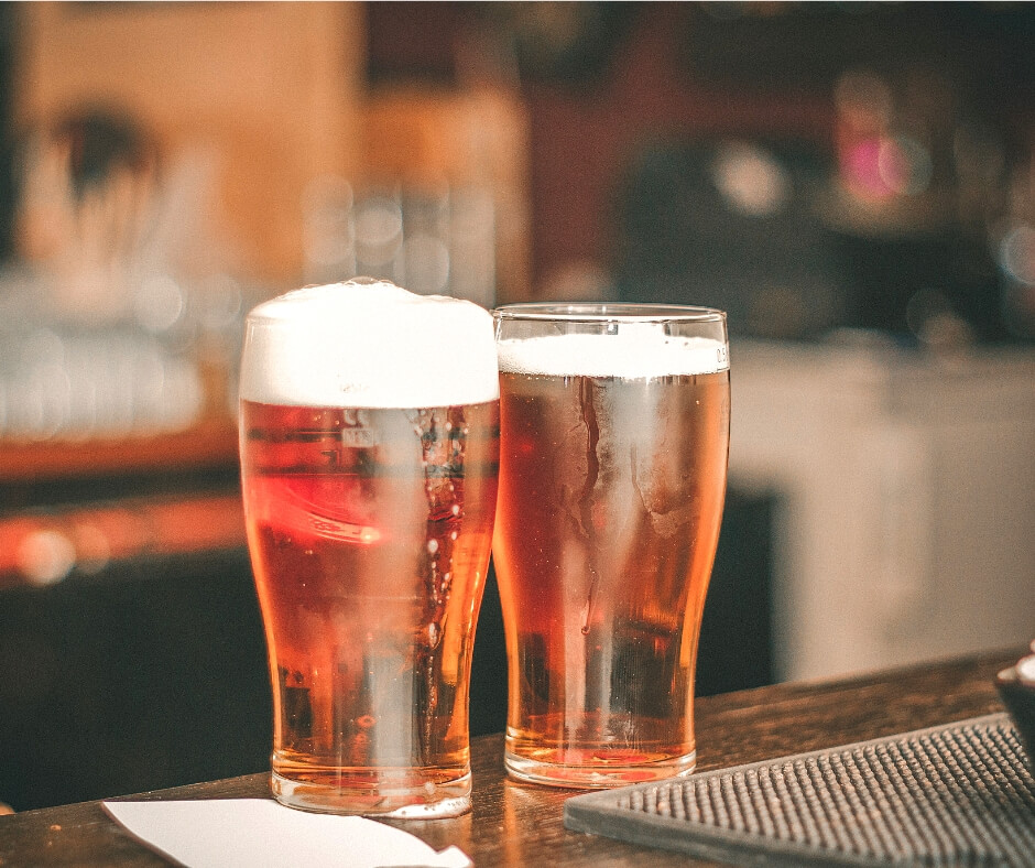 2 glasses of beer on a bar. There is a link between beer and breast cancer